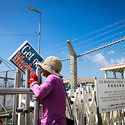 "OKINAWA, JAPAN - JUNE 17 : Anti U.S. Base protester with placard ""GET OUT MARINES"" stand in front of the gate of the Camp Schwab on June 17, 2016 in Nago, Okinawa, Japan. Protests have grown more intense in the past days due to the past incident of rape of a Japanese woman and drunk driving in Okinawa over American military presence in Japan. Photo: Richard A. de Guzman"