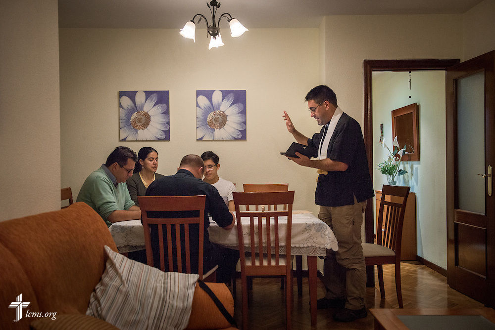 Jose Antonio (second from left) and his family, Sandra María and Juan José, along with the Rev. Adam Lehman, LCMS career missionary to Spain, receive the benediction during home worship by the Rev. David Warner, fellow career missionary, at the family's home Friday, Nov. 4, 2016, in Valladolid, Spain. LCMS Communications/Erik M. Lunsford
