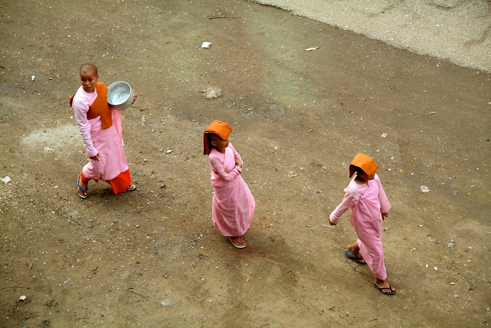 "The Buddhist Nuns in Myanmar are called Thilashins wich means ""possessor of morality"". They observe the ten precepts and are easy recognised by their pink robes, orange shawl, shaven head and metal alms bowl. Thilashins go out on alms rounds during the day of observance and receive uncooked rice or money."