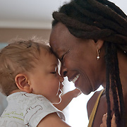 touching foreheads, a baby boy and his grandmother share a moment of bliss