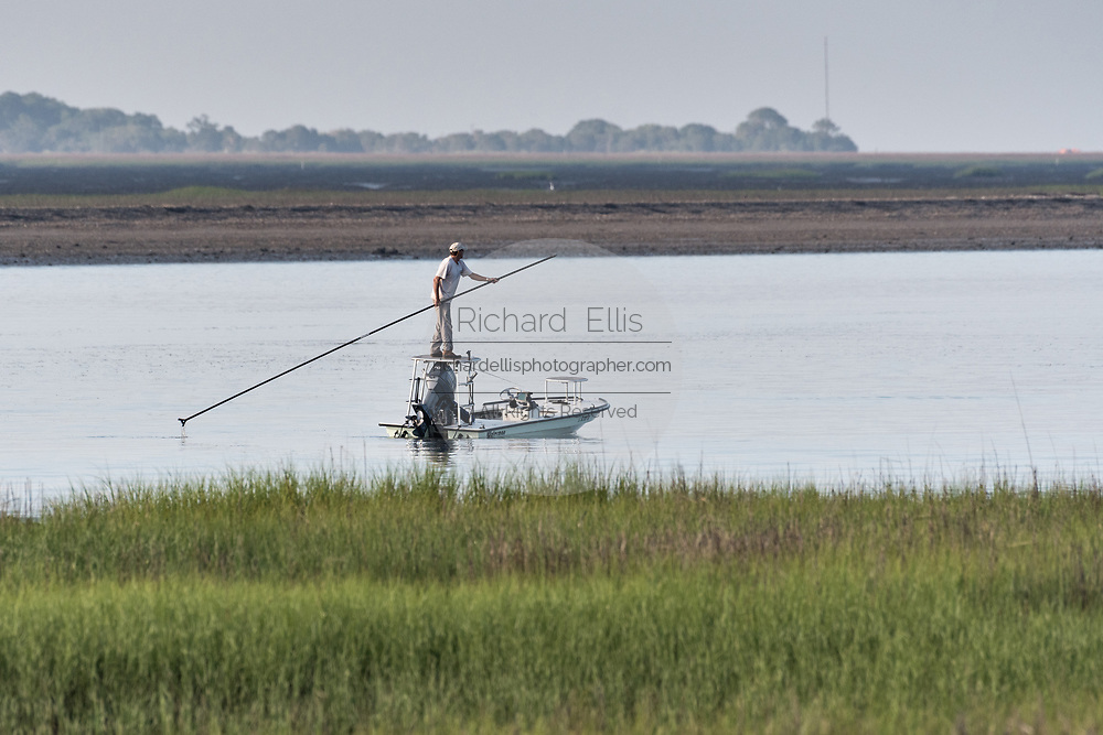A flats fisherman poles his small boat in the salt marshes of the Cape Romain National Wildlife Refuge near Charleston, South Carolina. The 66,287 acre National Wildlife Refuge encompass water impoundments, creeks, bays, emergent salt marsh and barrier islands most of which is only accessible by boat.