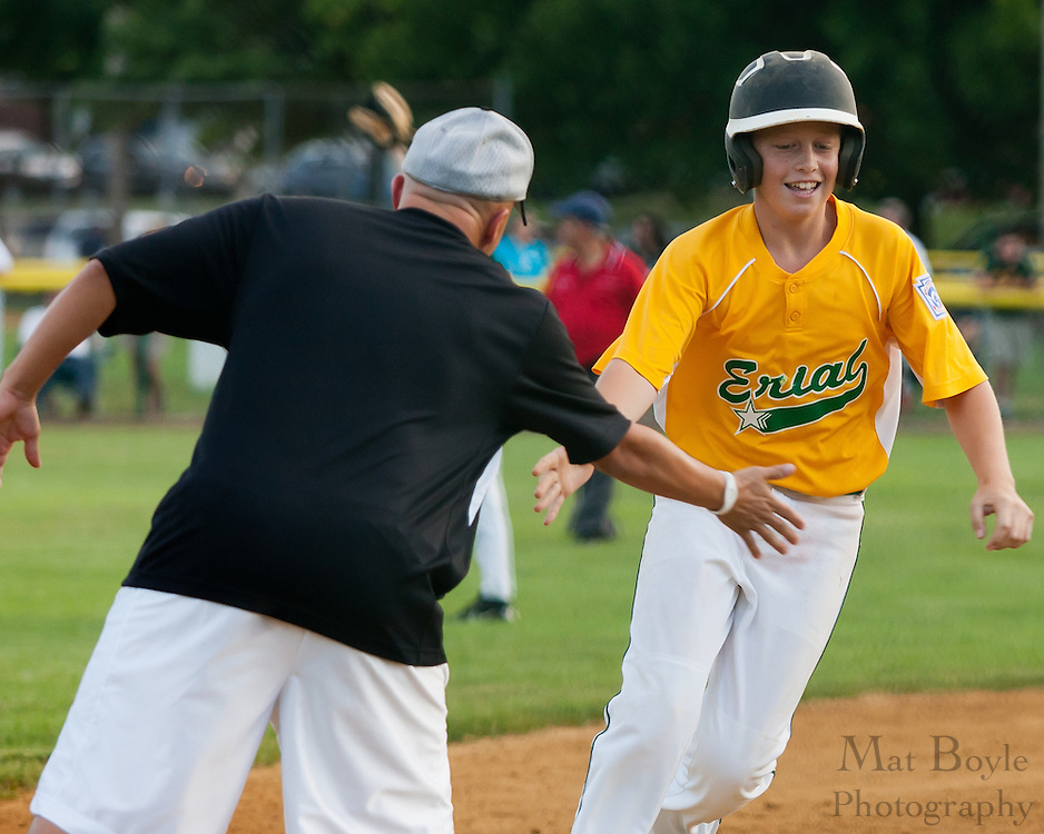 Erial's third base coach congratulates Jason Reynolds after he hits a   solo homerun after during the District 14 Little League final against Audubon held in Gloucester on Wednesday July 13th.