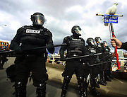 Portland riot police stand their ground as they block the end of the Morrison Bridge from anti-war protesters ho had vered off from their designed parade route in an effort to disrupt traffic.