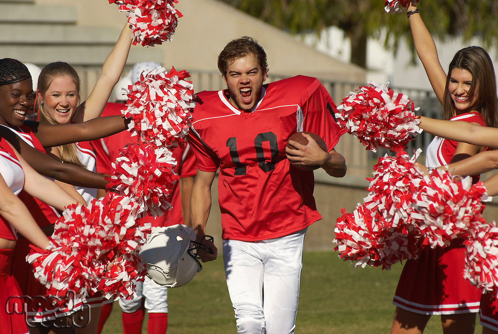 Football Player Running Through Cheerleaders