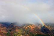 A vibrant rainbow forms during a late-afternoon rainstorm over Waimea Canyon on the Hawaiian island of Kauai. The canyon is 10 miles long and more than 3,500 feet deep. It was carved by runoff from Mount Waialeale, which gets more rain than any other spot on Earth.