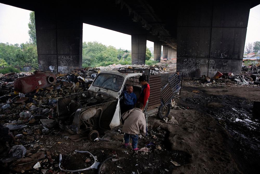 Children play in an abandoned, hand-made car underneath the Gazela Bridge in the Nova Gazela settlement.