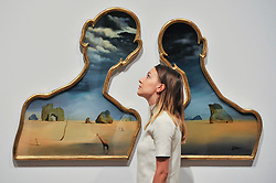 """© Licensed to London News Pictures. 03/10/2017. London, UK.   A staff member stands in front of """"Couple With Their Heads Full of Clouds"""", 1937, by Salvador Dali at the preview of """"Dali / Duchamp"""", a new exhibition of works by Salvador Dali and Michel Duchamp taking place at the Royal Academy of Arts in Piccadilly.  Over 80 artworks in different media are on display from 7 October to 3 January 2018.   Photo credit : Stephen Chung/LNP"""