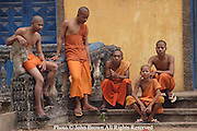 Buddhist monks and novices enjoy a relaxing afternoon on the steps of their temple in Kratie, Cambodia. Many of these young novice monks enter the temples as young boys and some eventually attend college and learn to speak English.