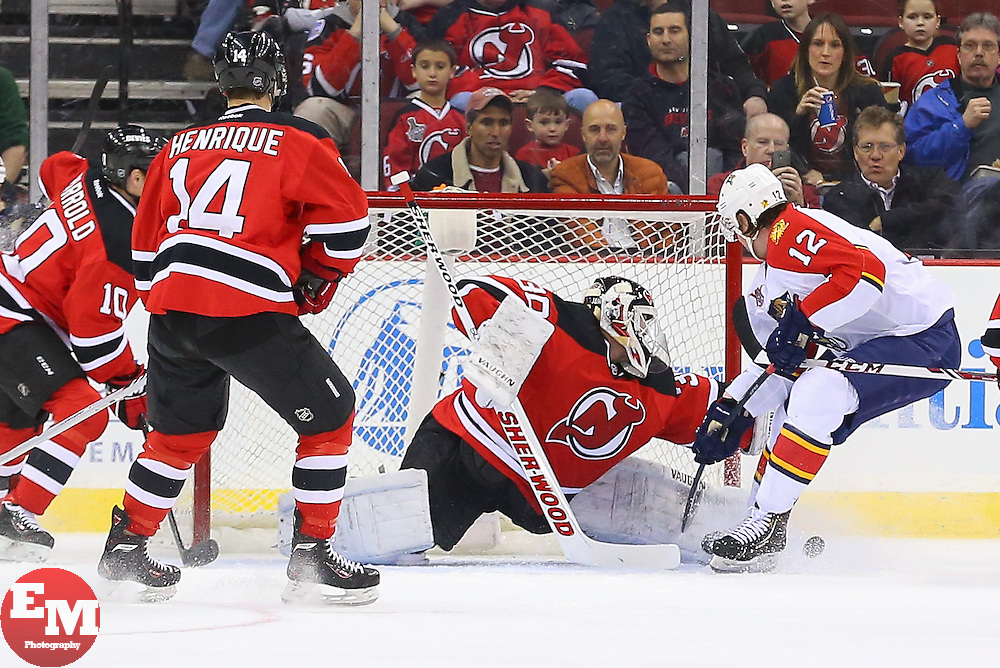 Mar 31, 2014; Newark, NJ, USA; New Jersey Devils goalie Martin Brodeur (30) makes a save on Florida Panthers right wing Jimmy Hayes (12) during the first period at Prudential Center.
