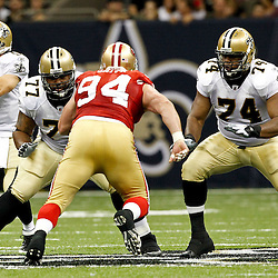 August 12, 2011; New Orleans, LA, USA; New Orleans Saints guard Carl Nicks (77) and offensive tackle Jermon Bushrod (74) protect quarter Drew Brees (9) from San Francisco 49ers defensive tackle Justin Smith (94) during the first half of a preseason game at the Louisiana Superdome. Mandatory Credit: Derick E. Hingle