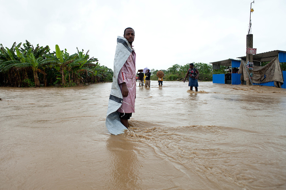 A man stands on a road flooded by rain from hurricane Tomas.