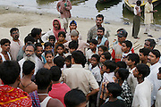 A young Nepalese boy studying sanskrit at an ashram in Varanasi was swimming with friends in the Ganges River and drowned. Here his friend (to the right of the man with the beard) who was swimming with him tells the authorities how he drowned right after the boy disappeared beneath the murky waters of the Ganges. His teacher called his parents in Kathmandu but did not tell the reason why. When his father, Bhim Prasad Bastola, arrived in Varanasi on a bus, he was told of the death of his 15-year-old son Chudamani Bastola and the cremation ceremony was held shortly thereafter.