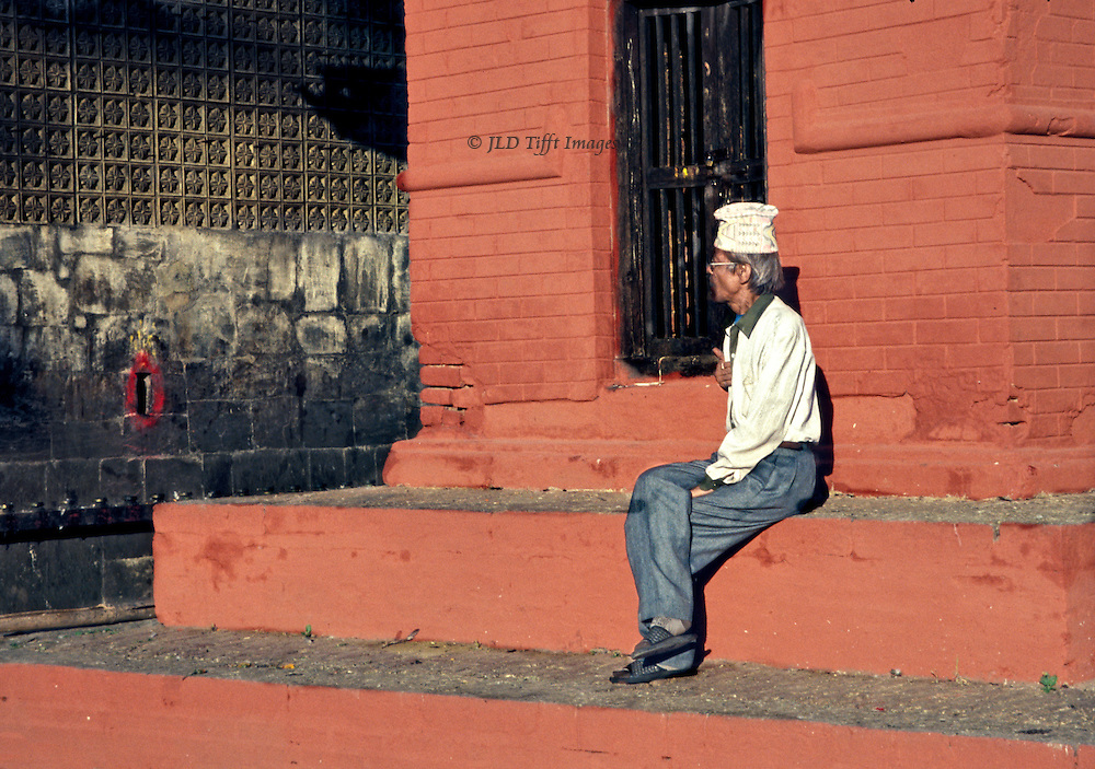 Hindu shrine in a Kathmandu street; seated Nepali man wearing a Dhaka Topi (traditional hat) contemplates red-painted niche in nearby wall.  He is a solitary and contemplative figure against the shrine background of freshly painted red brick..