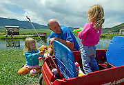 PRICE CHAMBERS / NEWS&amp;GUIDE<br /> Jim Wolfgang gets attacked by his daughters' squirtguns at the National Fish Hatchery pond in June. 3-year-old twins Sophi and Isabella spend each Saturday with one parent while the other works on the home in Teton Village.