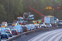 © Licensed to London News Pictures. 19/09/2019. Gerrards Cross, UK. Wreckage of a truck is recovered from the side of the M40 motorway in Buckinghamshire, the road traffic collision between and large goods vehicle and a car occurred at approximately 20:30BST between Junction 2 and Junction 1a of the M40 southbound carriageway. The southbound carriageway was closed for approximately 10 hours overnight whilst emergency services dealt with the incident. Credit: Peter Manning/LNP