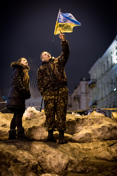 A man and a woman stand on a barricade, an ukrainian flag waving above their heads.