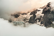 A glacier and the Italian side of the Mont Blanc massif breaks through the clouds on a stormy day.