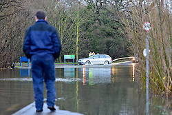 © Licensed to London News Pictures. 03/01/2014. Jacobs Well, UK A man watches as cars pass through flood water created by the River Mole bursting it's banks at Jacobs Well in Surrey today 3rd January 2013. Floods an heavy rain are continuing to effect travel and people across the country today. Photo credit : Stephen Simpson/LNP