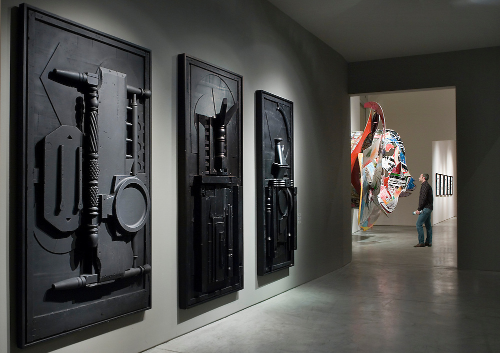sculptures by Louise Nevelson and Frank Stella with collector looking at art.