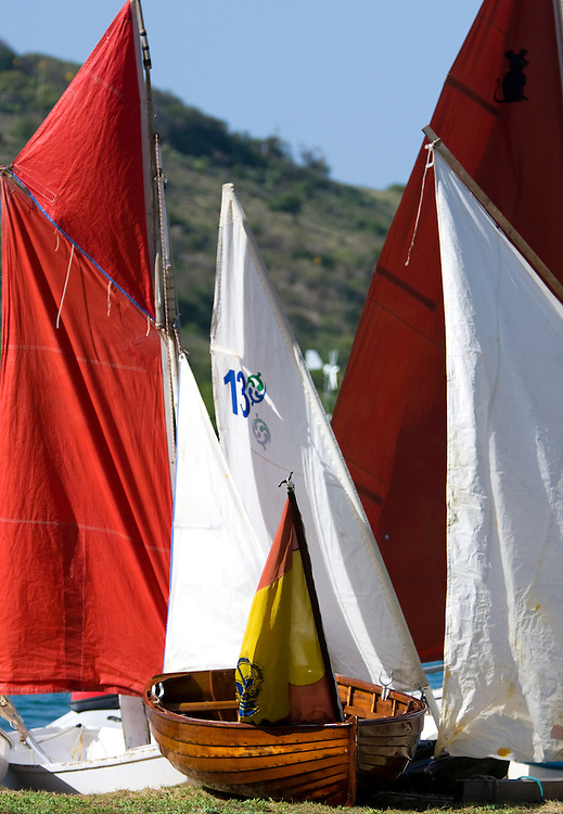 A dinghy with a Spanish flag sits on the shore surrounded by sails during the 2008 Antigua Classic Yacht Regatta . This race is one of the worlds most prestigious traditional yacht races. It takes place annually off the cost of Antigua in the British West Indies. Antigua is a yachting haven, historically a British navy base in the times of Nelson.