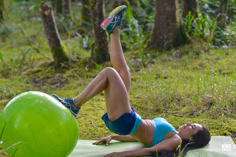 Hispanic brunette woman exercising with a green rubber ball in a forest.   May 29, 2014. (Kike Calvo via AP Images)
