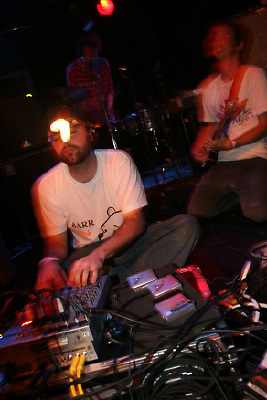 Animal Collective performing at The Knitting Factory on November 21, 2004. .Geologist - seated with light on his head.Avery Tare - on vocals standing with guitar and white t-shirt left of frame. .Deaken on guitar on the right side of frame.panda bear on drums.Photo Credit; Rahav Segev