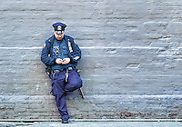 On duty cops relaxes on a wall and checks his cellphone