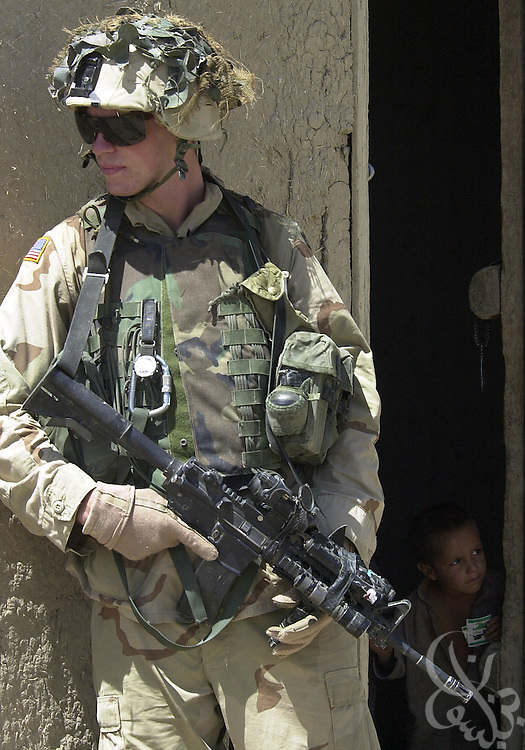 US Army soldiers from the 101st Airborne take up positions around the eastern Afghan village of Hesarak on July 16, 2002 during what the Army refers to as a 'sensitive site exploitation' mission or 'SSE'. The army says that Hesarak was raided for the first time four days ago when undisclosed intelligence materials were gathered. Today's raid was intended both to search for more materials and to provide some humanitarian aid to local residents.