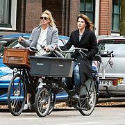 NLD/Amsterdam/20150525 - Kim van Kooten en vriendin fietsend door Amsterdam