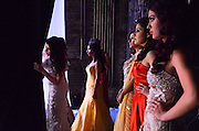 Contestants in the Miss Latina Illinois and Miss Teen Latina Illinois pageant watch their co-contestants from backstage as they perform in the evening gown portion of the contest. The pageant was held at the Athenaeum Theatre in Chicago on April 21, 2012.
