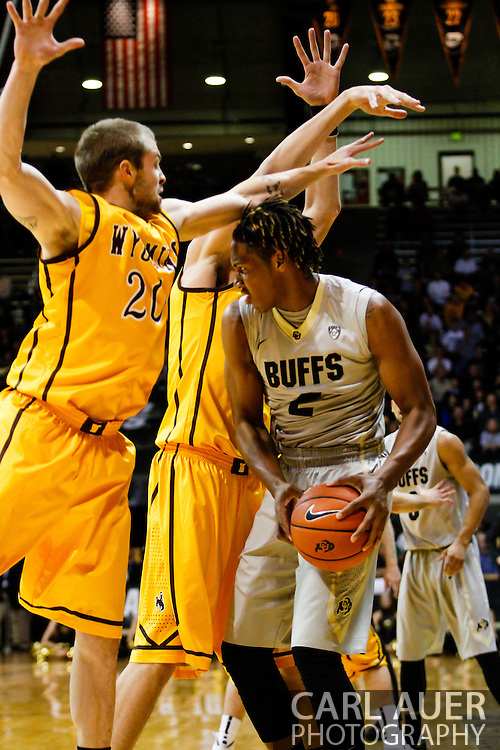 November 13th, 2013:  Colorado Buffaloes sophomore forward Xavier Johnson (2) attempts to get through the defense by University of Wyoming Cowboys senior guard Nathan Sobey (20) and junior forward Larry Nance Jr. (22) in the first half of the NCAA Basketball game between the University of Wyoming Cowboys and the University of Colorado Buffaloes at the Coors Events Center in Boulder, Colorado