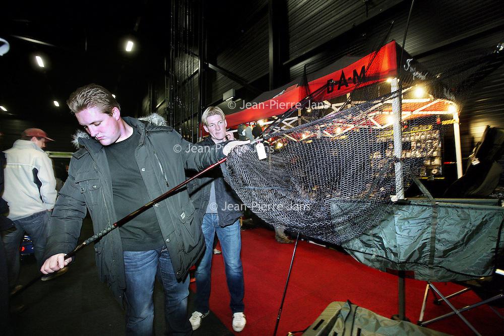 Nederland, Assen , 28 november 2010.Een kleine 3000 bezoekers vonden op zaterdag 27 en zondag 28 november 2010 de weg naar de beurs CarpevenTT in Assen. Met deze mooie opkomst kan de organisatie dan ook spreken van een succesvolle tweede editie van deze karperbeurs...De tweede editie van CarpevenTT stond in het teken van tal van activiteiten, acties en aantrekkelijke beursaanbiedingen. De georganiseerde viswedstrijd kon vanwege de vrieskou helaas niet plaatsvinden, maar dit werd binnen op de beursvloer dubbel en dwars goedgemaakt. Zo waren er verschillende lezingen van bekende karpervissers, was het gigantische aquarium gevuld met dikke karpers opnieuw aanwezig en vond er op de beursvloer een heuse Topvisser CarpevenTT voerbotenrace plaats...Men trying fishing equipment at the fair CarpevenTT, all about carps and sport fishing.