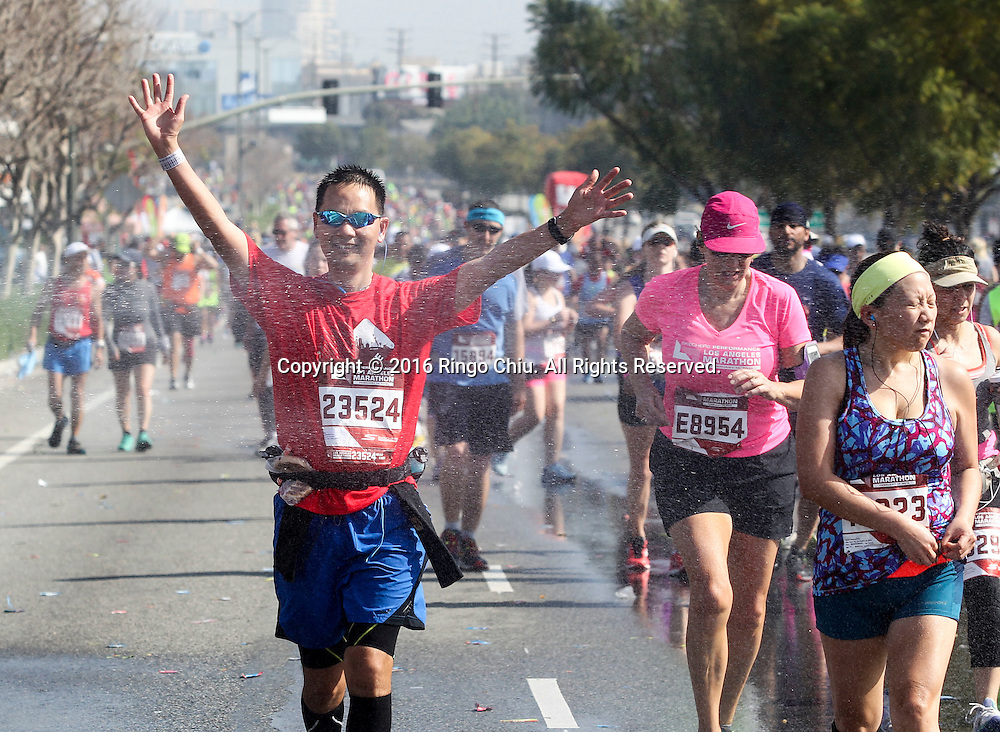 Runners run through a spray of water along Santa Monica Boulevard during the 31st Los Angeles Marathon in Los Angeles, Sunday, Feb. 14, 2016. The 26.2-mile marathon started at Dodger Stadium and finished at Santa Monica.  (Photo by Ringo Chiu/PHOTOFORMULA.com)<br /> <br /> Usage Notes: This content is intended for editorial use only. For other uses, additional clearances may be required.
