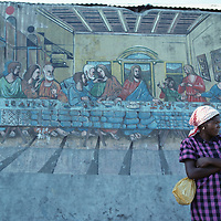 Haiti, Port-au-Prince, Woman stands in front of biblical mural outside cathedral in capital city