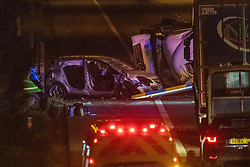 © Licensed to London News Pictures. 01/04/2020. Gerrards Cross, UK. A damaged car and the front of an overturned HGV on the northbound carriageway of the M40 motorway between J1 and J2. The M40 motorway was closed in both directions due to a Road Traffic collision involving a heavy goods vehicle and at least to cars. Photo credit: Peter Manning/LNP