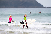 Eveline Hooft (NDL) and Lauren Sandland (UK) making their way out to the start of Round 2 Heat during the 2019 Boardmasters Roxy Pro Surf Competition, WSL Qualifier at Fistral Beach, Newquay, Cornwall on 8 August 2019.