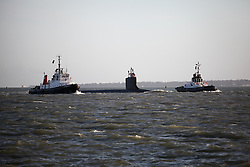 © Licensed to London News Pictures. 22/02/2014. Portsmouth, Hampshire, UK. The American Virginia-Class nuclear powered submarine, USS New Hampshire escorted by two tugs into Portsmouth, Hampshire, UK today 22nd February 2014. Photo credit : Rob Arnold/LNP