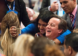 © Licensed to London News Pictures. 30/09/2014. Birmingham, UK . British Prime Minister David Cameron takes a selfie with delegates ahead of The Mayor of London's Speech. The Conservative Party Conference in Birmingham 30th September 2014. Photo credit : Stephen Simpson/LNP