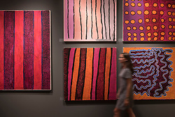 © Licensed to London News Pictures. 29/06/2016. London, UK.  A woman walks in front of vividly coloured aboriginal contemporary art on the JGM Art stand at the preview, in Chelsea, of Masterpiece London, the leading international fair for art and design from antiquity to the present day with works from 154 world-renowned exhibitors on sale.  The fair is open until 6 July.Photo credit : Stephen Chung/LNP