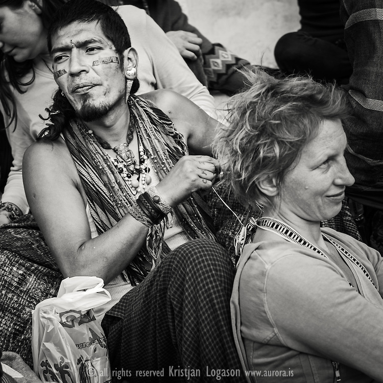 Tattooed man putting braises in the hair of a red haired woman at the square in central San Cristobal