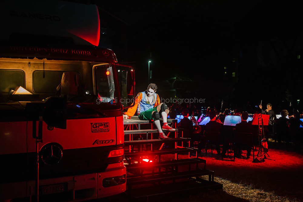 ROME, ITALY - 27 JUNE 2017: Opera singer Murat Carlo Feola (in the role of Leporello) is seen here on stage performing in the &quot;Don Giovanni OperaCamion&quot;, an open-air opera performed on a truck in San Basilio, a suburb in Rome, Italy, on June 27th 2017.<br /> <br /> Director Fabio Cherstich&rsquo;s idae of an &ldquo;opera truck&rdquo; was conceived as a way of bringing the musical theatre to a new, mixed, non elitist public, and have it perceived as a moment of cultural sharing, intelligent entertainment and no longer as an inaccessible and costly event. The truck becomes a stage that goes from square to square with its orchestra and its company of singers in Rome. <br /> <br /> &ldquo;Don Giovanni Opera Camion&rdquo;, after &ldquo;Don Giovanni&rdquo; by Wolfgang Amadeus Mozart is a new production by the Teatro dell&rsquo;Opera di Roma, conceived and directed by Fabio Cherstich. Set, videos and costumes by Gianluigi Toccafondo. The Youth Orchestra of the Teatro dell&rsquo;Opera di Roma is conducted by Carlo Donadio.