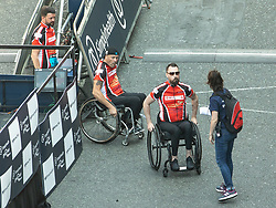 © Licensed to London News Pictures . 20/05/2018 . Manchester , UK . MARTIN HIBBERT (2nd from right), who was paralysed in the Manchester Arena bombing , seen on Portland Street in Manchester City Centre at the start of the Great Manchester Run . A minute of silence is held ahead of the start of the race to mark the first anniversary of the Manchester Arena bombing , which killed 22 and seriously injured dozens more , at an Ariana Grande concert on 22nd May 2017 . Photo credit : Joel Goodman/LNP
