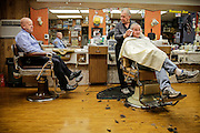 Joliet Police Officer Mike Reilly talks with barber Bob Babich at Banana Joe's Barber Shop, Thursday Dec. 18, 2014, in Joliet Ill.As part of the Neighborhood-Oriented Policing Team, Rielly likes to maintain a personal relationship with people in his patrol area.