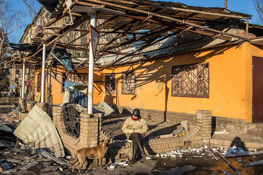 DEBALTSEVE, UKRAINE - FEBRUARY 20: A woman sits by a damaged building on the central square on February 20, 2015 in Debaltseve, Ukraine. Ukrainian forces withdrew from the strategic and hard-fought town after being effectively surrounded by pro-Russian rebels, though fighting has caused widespread destruction. (Photo by Brendan Hoffman/Getty Images) *** Local Caption ***