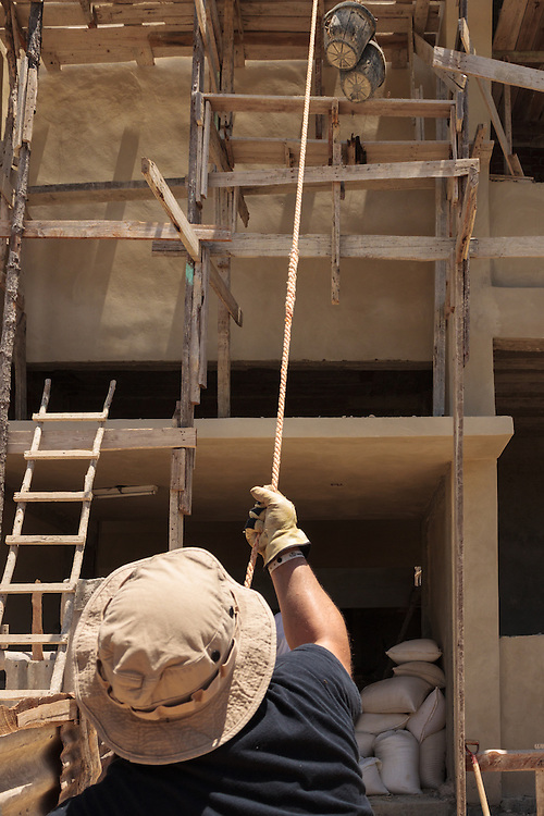 construction man pulling rope on pulley bucket of gravel
