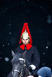 © Licensed to London News Pictures. 11/02/2017. London, UK. A soldier on duty at Horse Guards Parade whilst snowing in London on Saturday, 11 February 2017. Photo credit: Tolga Akmen/LNP