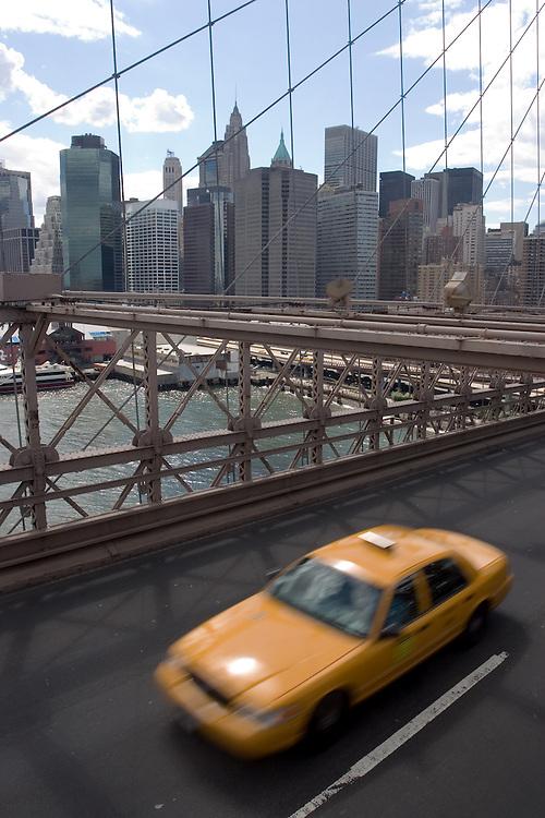 A tipical New York's yellow cab runs through Brooklyn bridge at high speed. <br /> <br /> Un taxi amarillo, t&iacute;pico de Nueva York cruza a toda velocidad el puente de Brooklyn, con Manhattan al fondo.