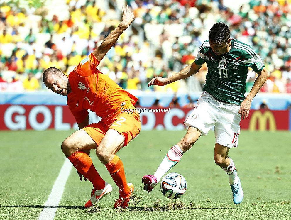 29.06.2014. Fortaleza, Brazil. Netherlands Ron Vlaar (L) challenges Mexicos Oribe Peralta during to a Round of 16 match between Netherlands and Mexico of 2014 FIFA World Cup at the Estadio Castelao Stadium in Fortaleza, Brazil, on June 29, 2014.