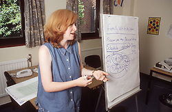 Teacher using flipchart to teach adult education class,