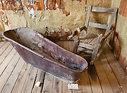 A plunge bath tub and old wooden rocking chair sit in a bare room with peeling wallpaper in the former gold mining town of Custer which dates from 1879-1910. Custer Historic Site now preserves this ghost town near Stanley, Idaho, USA. The city of Custer was named after General George Armstrong Custer, who was killed in battle in 1876. Custer is now part of the Land of the Yankee Fork State Park and Challis National Forest Historic Area.